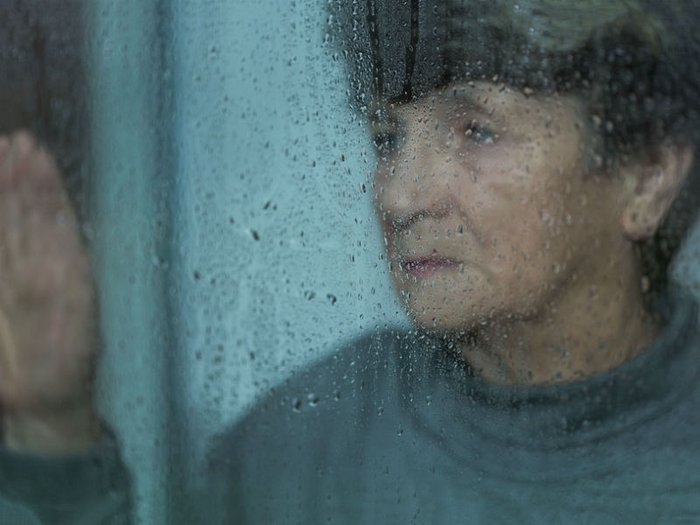 A grieving woman reflects on her sadness, as she looks through a rain-streaked window