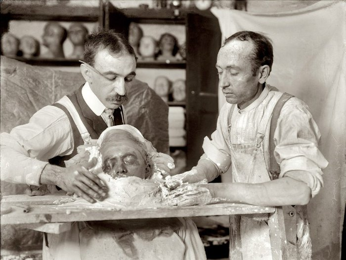 Black and white photo of two men in a workshop making a death mask, circa 1908