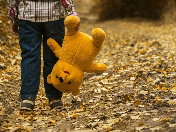 Grieving child carrying a teddy bear
