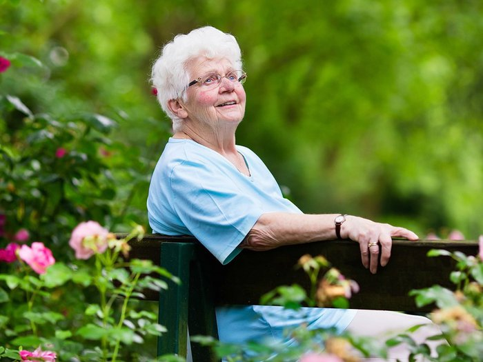 A lady sits in contemplation on a bench, in a  memory garden planted with roses