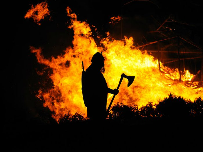 A viking warrior is silhouetted by a flaming funeral pyre