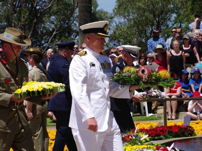 Photo of officers in the Australian army, navy and air forces laying wreaths at a remembrance day service
