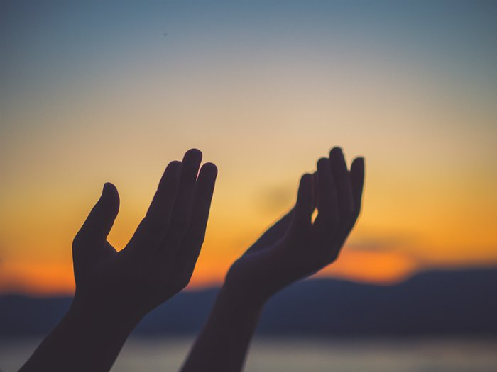 open hands, praying at sunset