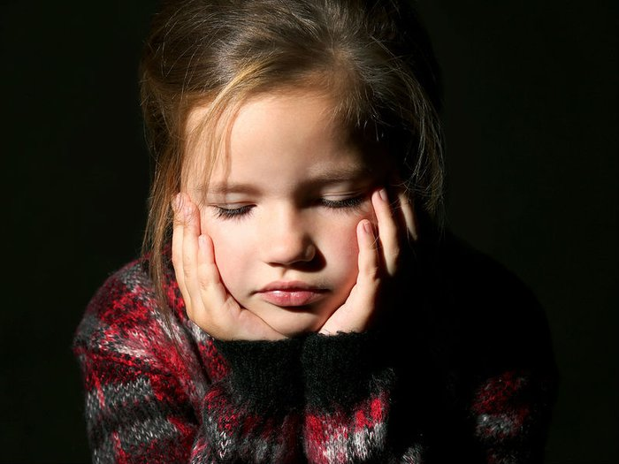 A little girl looks sad and pensive