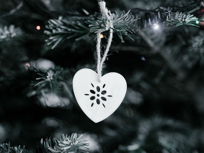 Close-up of a white heart shaped direction hanging on a Christmas tree