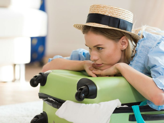 A young woman with a half-packed suitcase is lost in thought
