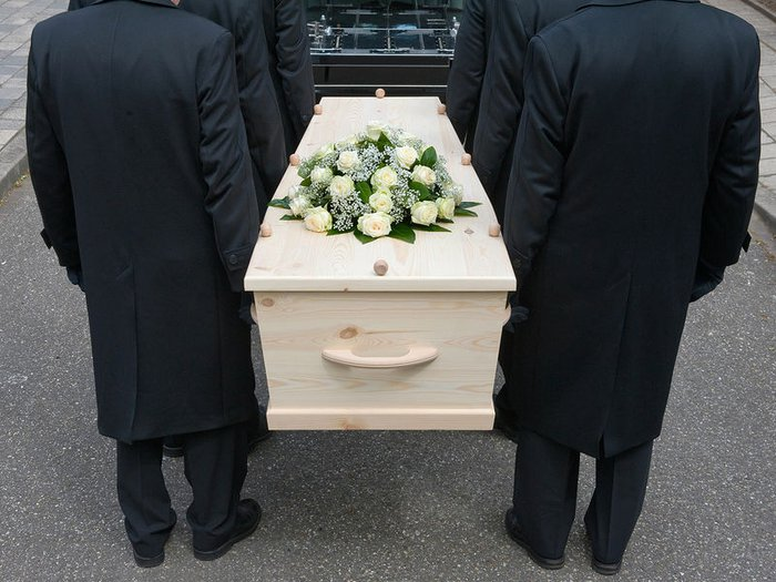 Pallbearers carrying a coffin to the hearse