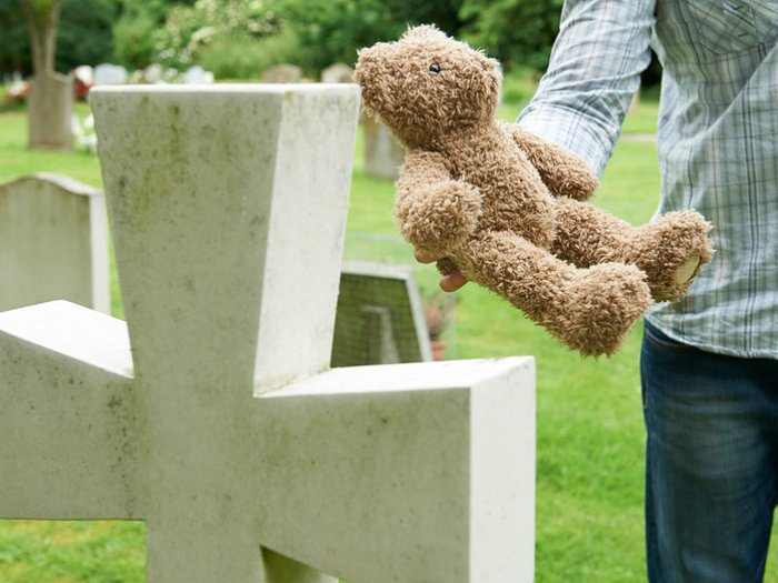 Grieving father placing teddy bear on child's grave