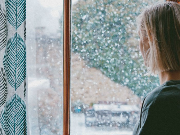 a woman looks out of a rainy window