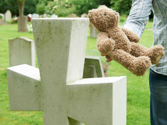 Bereaved father placing teddy bear on child's grave