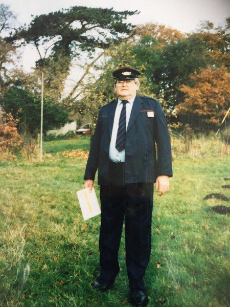 Stuart in his Postman uniform, stood in his garden.
