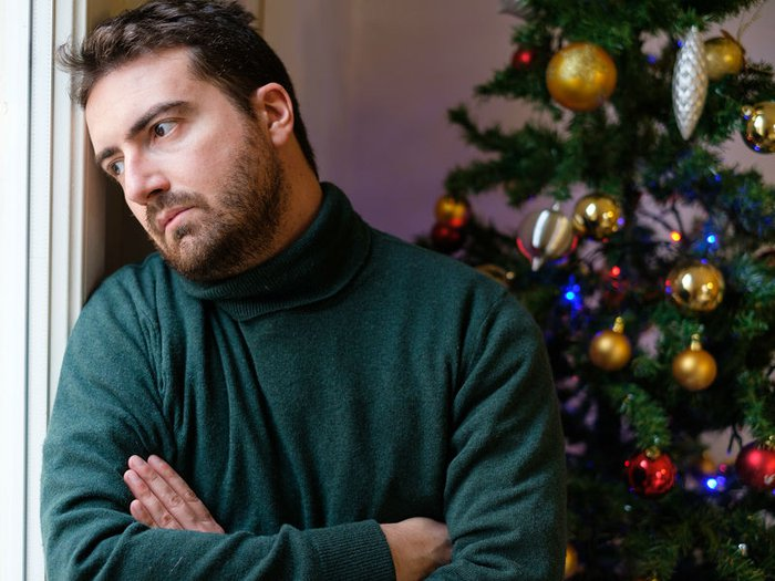 A bereaved man takes in sad news, in a room decorated for Christmas
