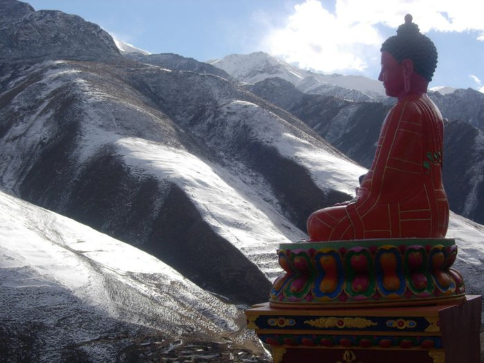 Tibetan Buddhist statue overlooking Himalayan mountains