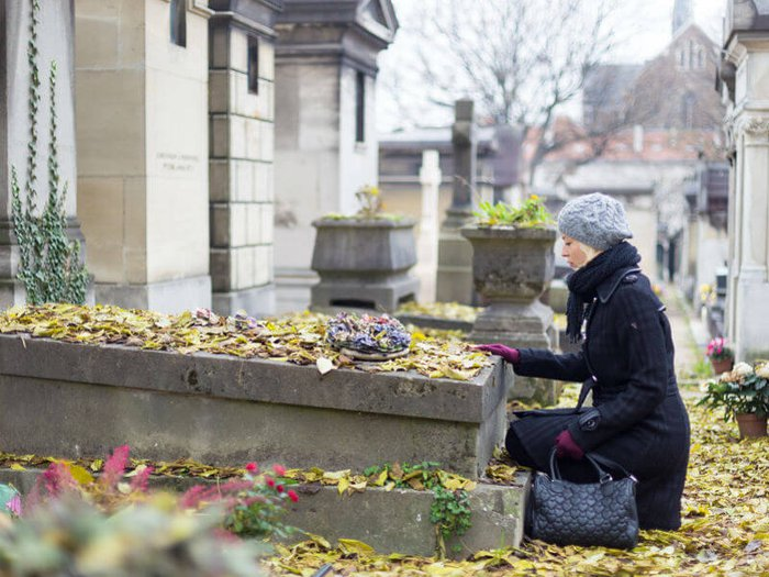 Grieving woman visiting loved one's grave
