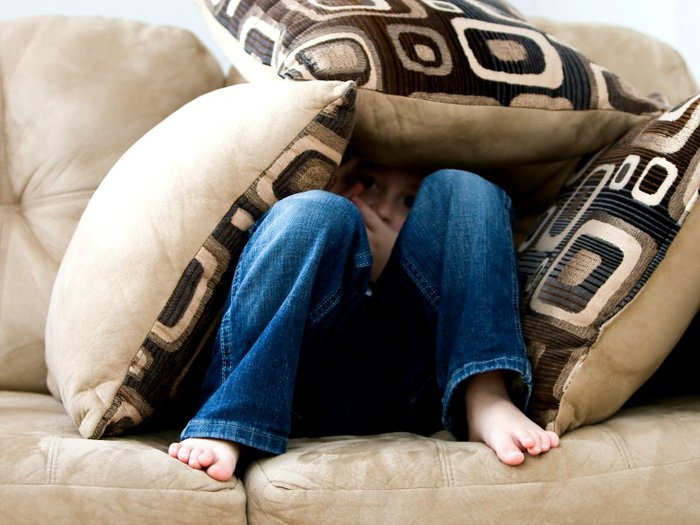 A sad child hidden in a den of cushions on the sofa