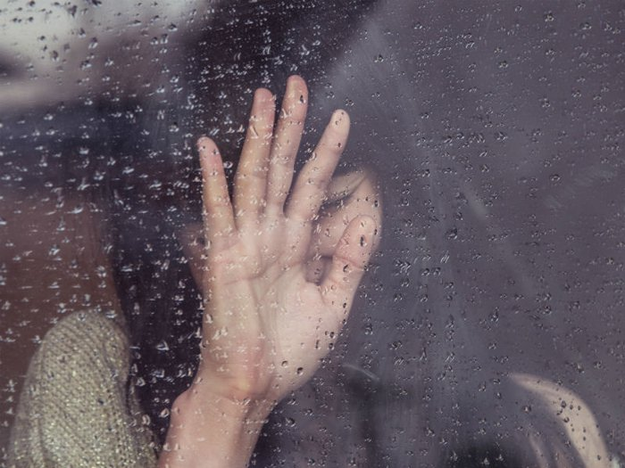 Grieving woman looking through a window