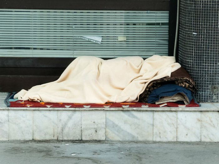 A person sleeping in a doorway