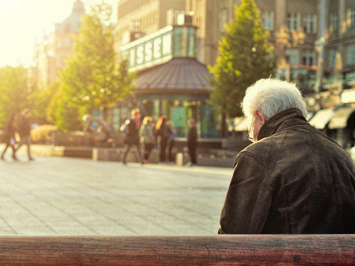 Elderly man sitting alone on a bench