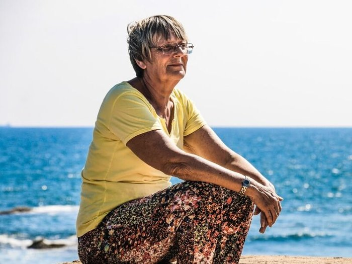 Older woman in a yellow top and floral trousers sitting on the beach by the sea