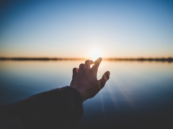 Picture of low sun above a lake with an arm reaching out from bottom left corner and fingers