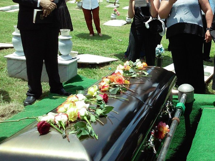 People standing around a coffin with flowers on top before it is lowered into a grave