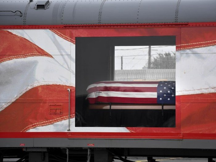 Close-up of carriage on George H.W. Bush's funeral train, with doors opening showing his coffin covered with the American flag