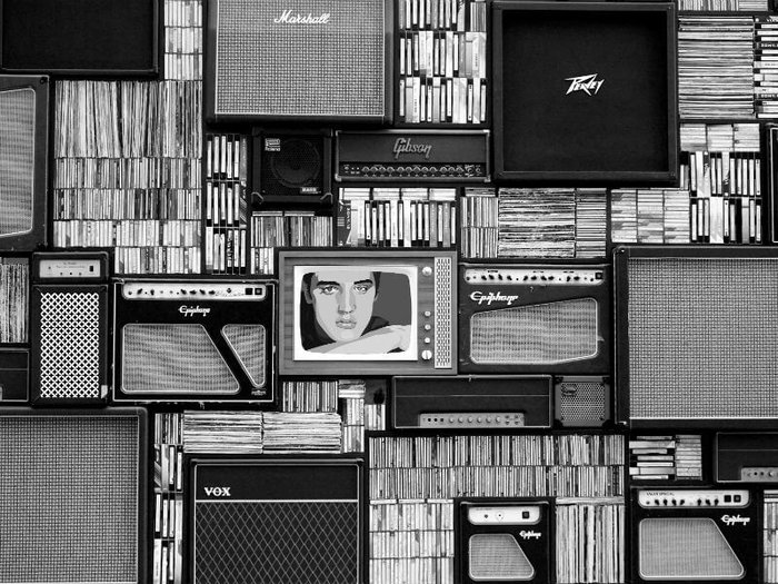 A wall full of CDs, vinyl records, TVs and amplifiers