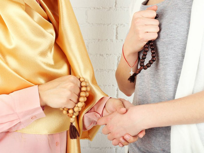Two women of different faiths shaking hands