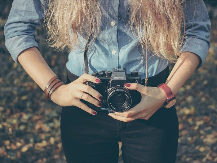 A young woman takes a photograph