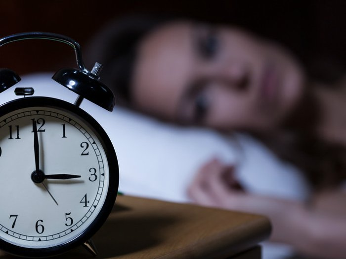 Woman lying in bed unable to sleep due to grief